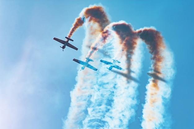 Drei leichtmotorflugzeuge führen kunstflug aus - eine tote schleife. die helle sonne beleuchtet die flugzeuge und die schatten fallen auf den rauch, den sie am himmel hinterlassen. Premium Fotos