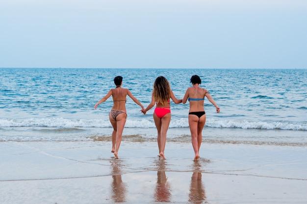 Drei lesbische freundin mädchen laufen am strand im meer zurück Premium Fotos