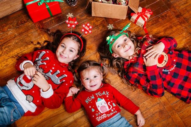 Drei lustige kleine schwestern liegen zu hause auf dem boden Premium Fotos