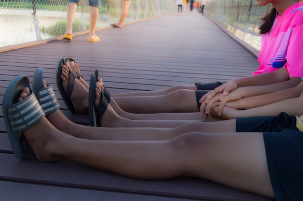 Drei mädchen, die hände, sitzen auf einer holzbrücke halten. Premium Fotos