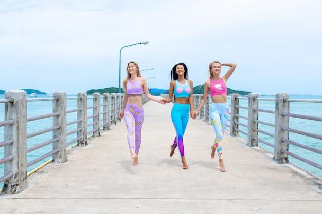 Drei mädchen entspannen sich auf dem pier und werfen in der modernen eignungskleidung auf. Premium Fotos