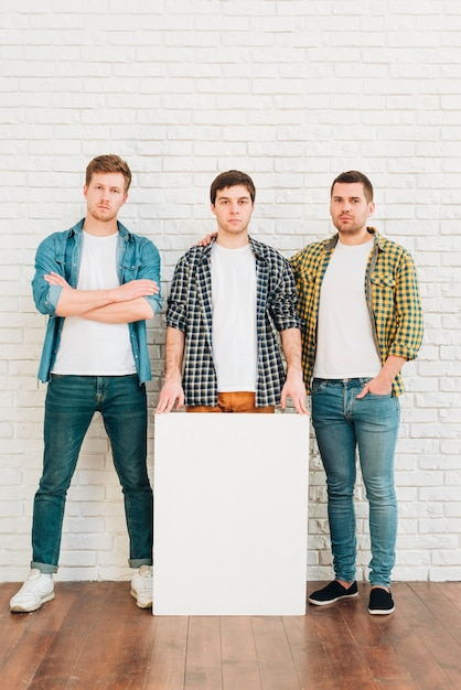 Drei männliche freunde mit dem weißen leeren plakat, das kamera betrachtet Kostenlose Fotos