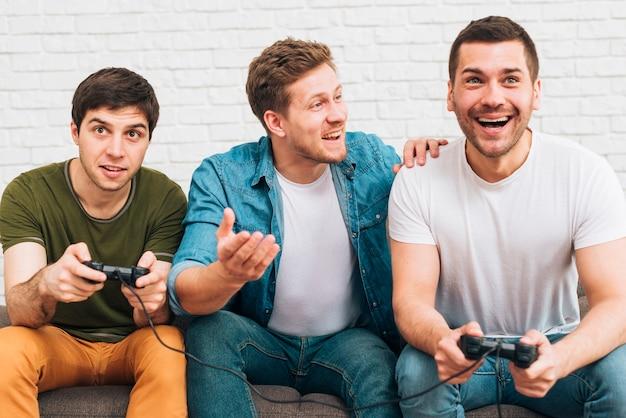 Drei männliche freunde sitzen zusammen und genießen das videospiel Kostenlose Fotos