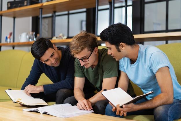 Drei mitschüler, die lehrbuch lesen und für prüfung sich vorbereiten Kostenlose Fotos