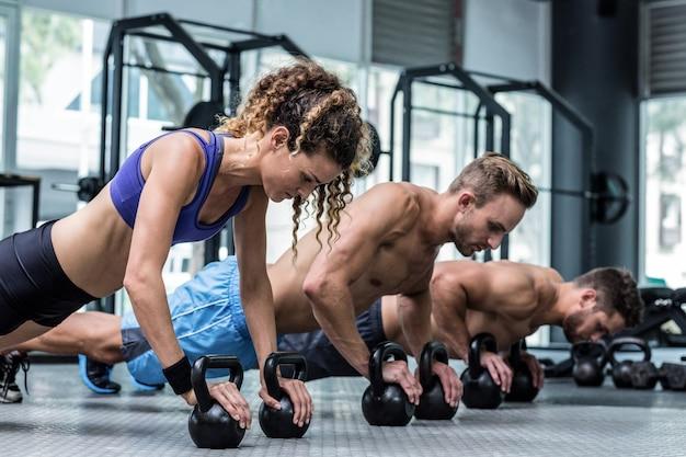 Drei muskulöse athleten auf einer plankenposition Premium Fotos