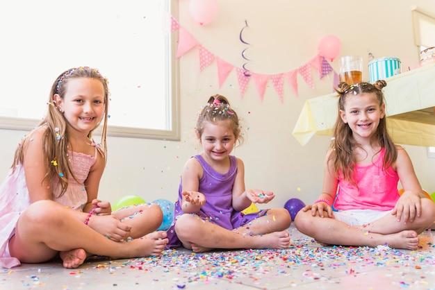 Drei nette mädchen, die auf dem boden genießt in einer party sitzen Kostenlose Fotos