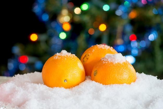 Drei orangen im schnee mit weihnachtsdekor Premium Fotos