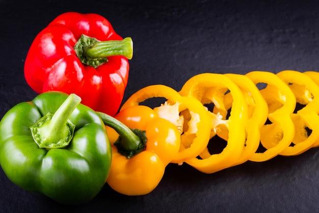 Drei paprika auf einem holztisch, gemüsesalat kochen Premium Fotos