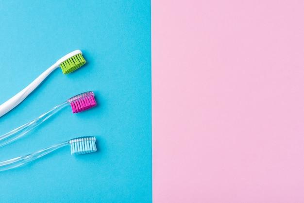 Drei plastikzahnbürsten auf einem bunten blauen und rosa hintergrund, abschluss oben Premium Fotos