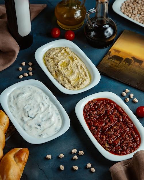 Drei platten mit türkischen beilagen werden im restaurant serviert Kostenlose Fotos