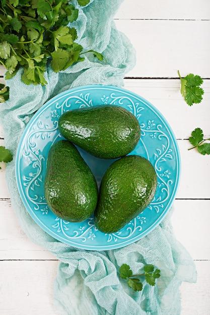 Drei reife avocados auf einem holztisch. gesundes lebensmittelkonzept. ansicht von oben Kostenlose Fotos
