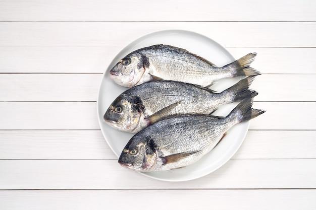 Drei rohe frische doradofische auf weißer platte. Premium Fotos