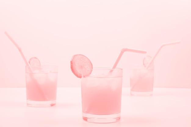 Drei rosa cocktailgläser auf farbigem hintergrund Kostenlose Fotos