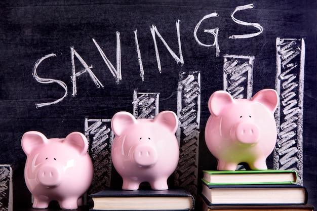 Drei rosa piggy banken, die auf büchern nahe bei einer tafel mit einsparungsdiagramm stehen. Kostenlose Fotos