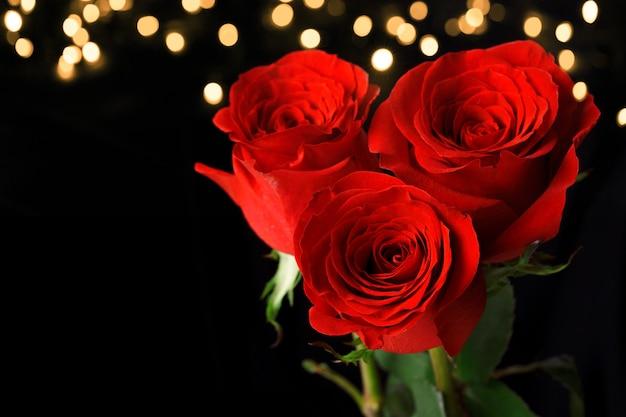 Drei rote rosen auf dunkler oberfläche Premium Fotos