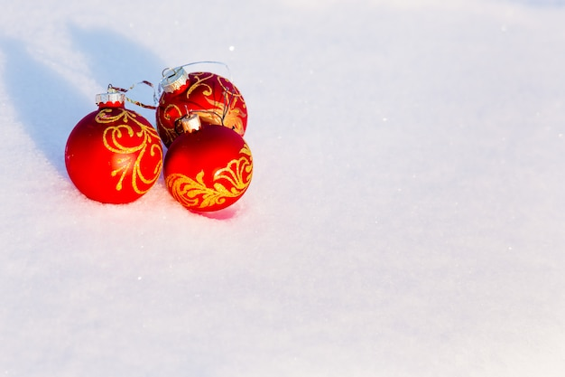 Drei rote weihnachtskugeln auf schnee Premium Fotos
