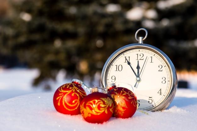 Drei rote weihnachtskugeln und wath auf einem schnee. Premium Fotos