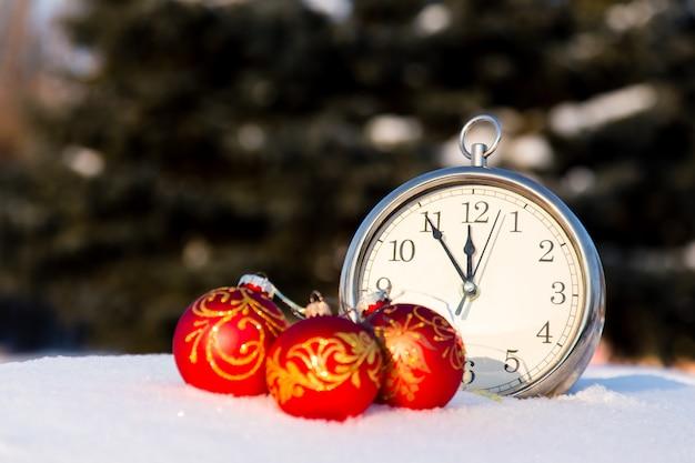 Drei rote weihnachtskugeln und wath auf schnee Premium Fotos