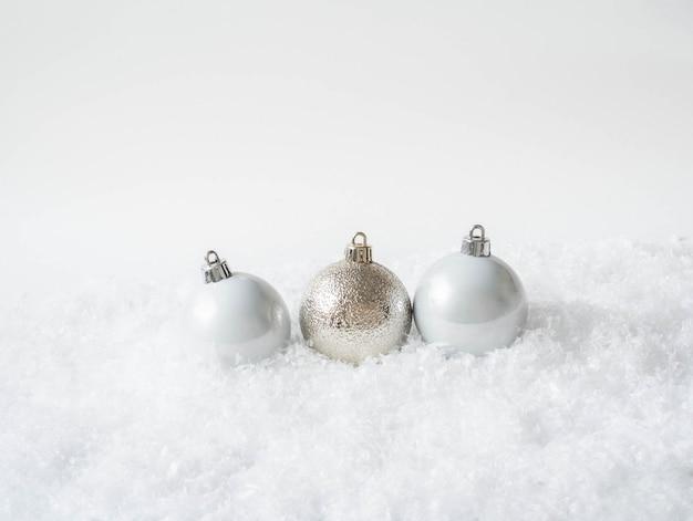 Drei runde weihnachtsbälle im schnee. frohe weihnachten oder happy new year zusammensetzung. kopieren sie platz Premium Fotos