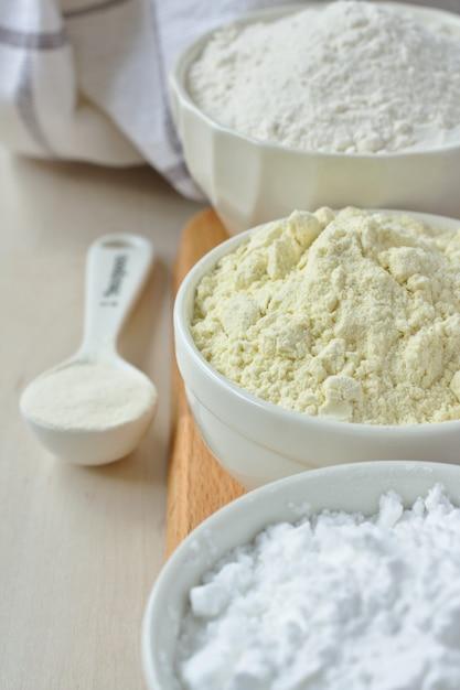 Drei schalen mit glutenfreiem mehl - reismehl, hirsemehl und kartoffelstärke und löffel mit xanthangummi Premium Fotos