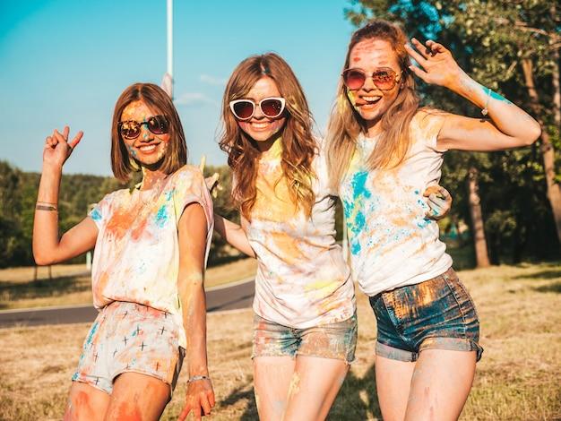 Drei schöne lächelnde mädchen, die auf holi party aufwerfen Kostenlose Fotos