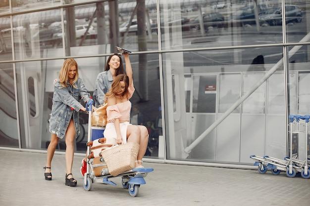 Drei schöne mädchen, die den flughafen bereitstehen Kostenlose Fotos