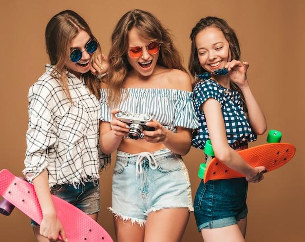 Drei schöne stilvolle lächelnde mädchen mit bunten pennyskateboards. frauen in sommerkleidung kariertes hemd. fotografieren mit einer retro-fotokamera Kostenlose Fotos