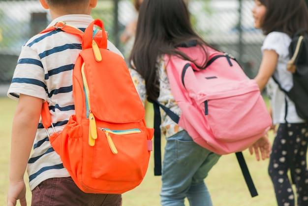 Drei schüler der grundschule gehen hand in hand. junge und mädchen mit schultaschen hinter dem rücken. beginn des schulunterrichts. warmer tag des herbstes. zurück zur schule. kleine erstklässler Kostenlose Fotos