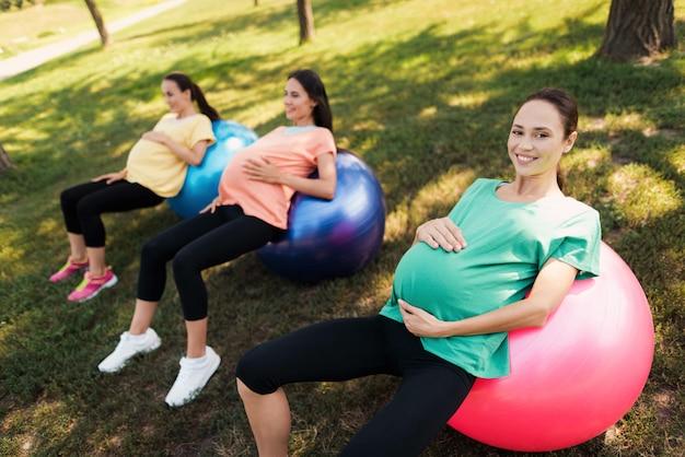 Drei schwangere frauen liegen auf yogabällen im park Premium Fotos