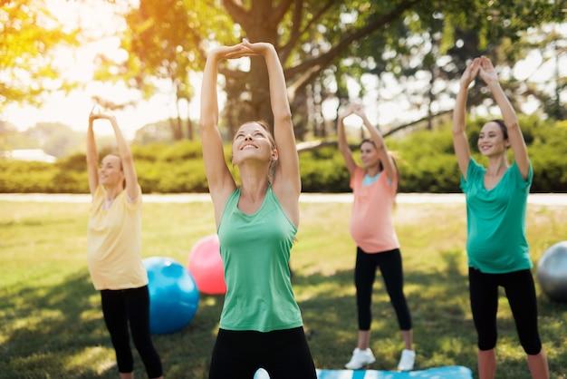 Drei schwangere frauen und ihr trainer bei einem yoga im park. Premium Fotos