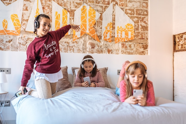 Drei schwestern, die miteinander spielen, liegend im bett zu hause, hörend musik Premium Fotos