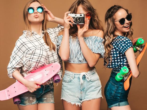 Drei sexy schöne stilvolle lächelnde mädchen mit bunten pennyskateboards. frauen in der karierten hemdkleidungsaufstellung des sommers. modelle, die fotos auf retro- fotokamera machen Kostenlose Fotos