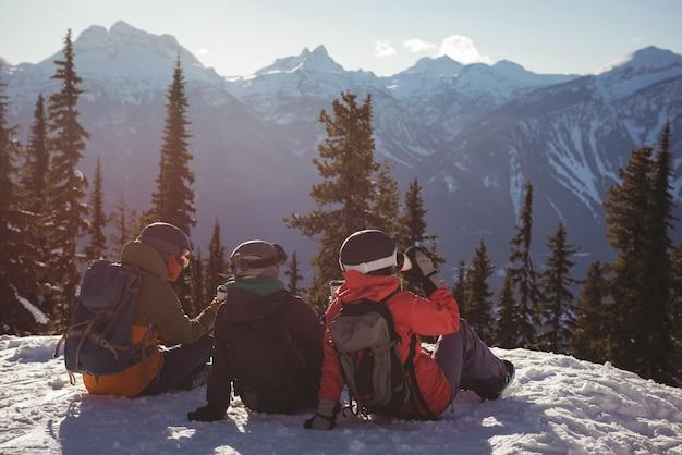 Drei skifahrer, die sich auf schneebedecktem berg entspannen Kostenlose Fotos
