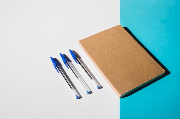Drei stifte und geschlossenes buch auf dem doppelten weißen und blauen hintergrund Kostenlose Fotos