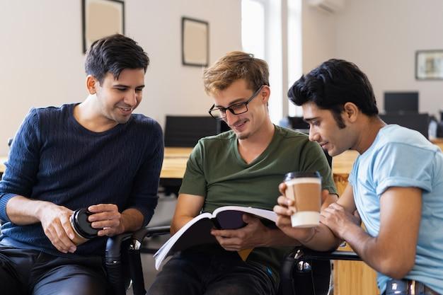 Drei studenten, die zusammen lehrbuch lesen und trinken Kostenlose Fotos