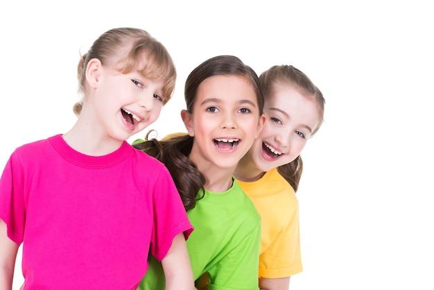 Drei süße kleine süße lächelnde mädchen in bunten t-shirts stehen hintereinander auf weißem hintergrund. Kostenlose Fotos