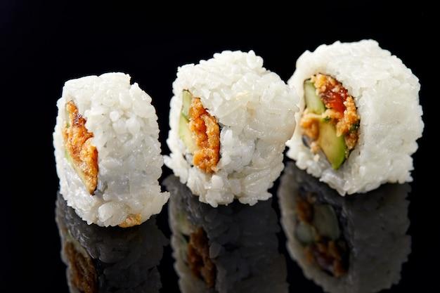 Drei sushi in einer reihe auf schwarzem mit reflexion Premium Fotos