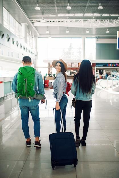 Drei touristen mit gepäck im flughafen, rückansicht. passagiere mit gepäck im flugterminal Premium Fotos