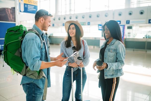 Drei touristen mit gepäck warten auf den abflug am flughafen. passagiere mit gepäck im flugterminal Premium Fotos