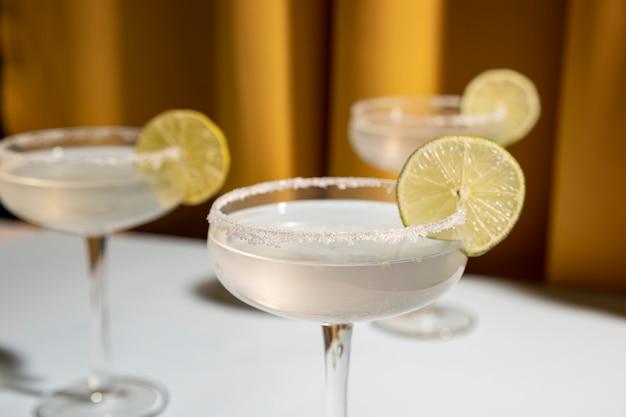 Drei untertassengläser margarita-cocktail schmücken mit kalk auf tabelle Kostenlose Fotos