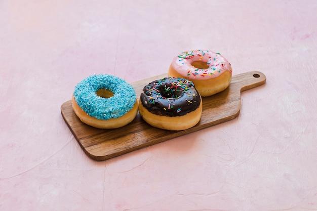Drei verschiedene art von donuts auf hölzernen schneidebrett Kostenlose Fotos