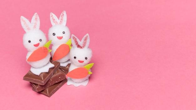 Drei weiße häschen mit karotte auf schokoladenstücken über dem rosa hintergrund Kostenlose Fotos