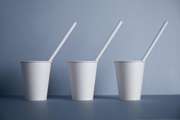 Drei weiße pappbecher ohne verschluss zum mitnehmen mit trinkhalmen in der mitte Kostenlose Fotos