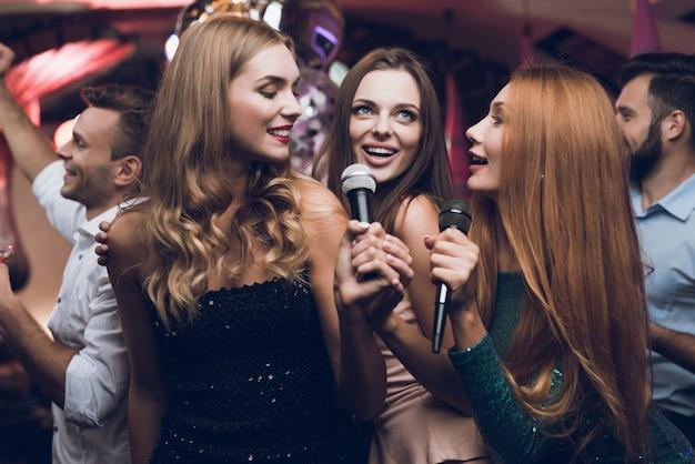 Drei wunderschöne mädchen singen in einem karaoke-club Premium Fotos