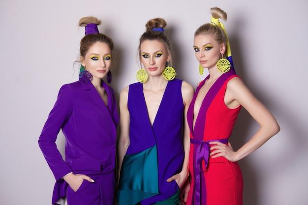 Drei wunderschöne models mit farbenfrohem make-up und designer-outfits Premium Fotos