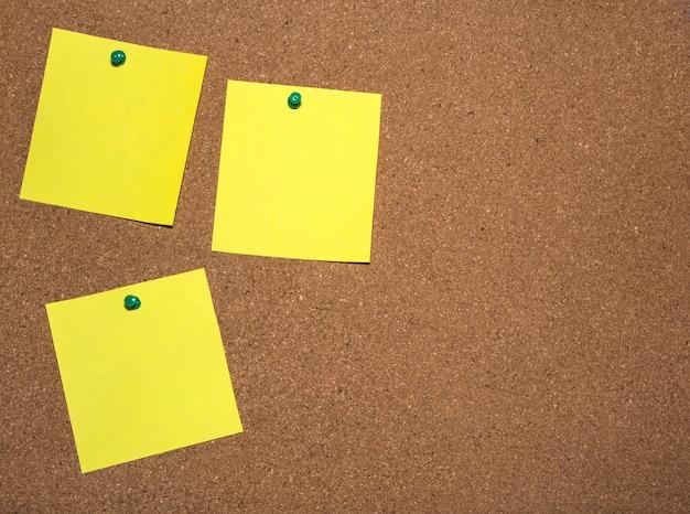 Drei zettel sind zum schreiben auf eine pinnwand gesteckt Premium Fotos