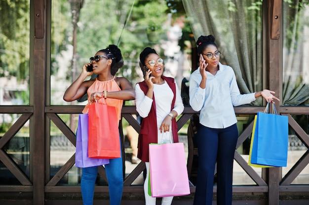 Drei zufällige afroamerikanermädchen mit dem farbigen einkaufstaschegehen im freien. stilvolle schwarze frau, die am handy kauft und spricht. Premium Fotos
