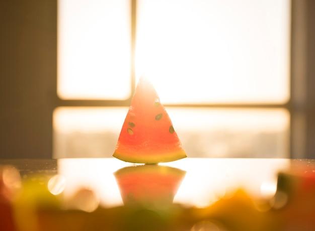 Dreieckige form der wassermelone mit samen auf reflektierendem schreibtisch im hellen sonnenlicht Kostenlose Fotos