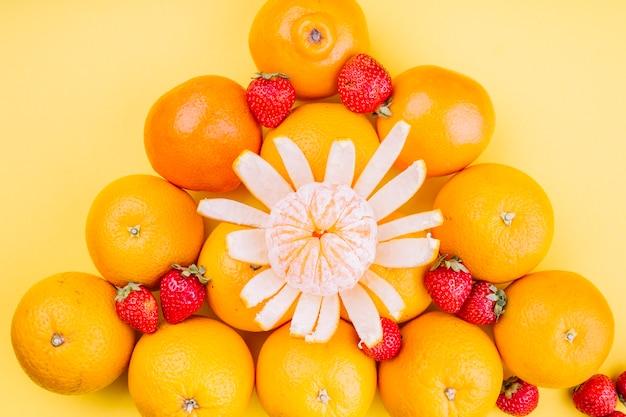 Dreieckige orangen mit erdbeeren auf gelbem hintergrund Kostenlose Fotos