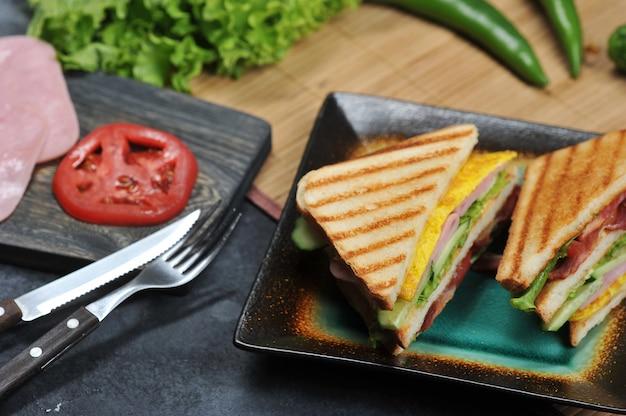 Dreieckige sandwiches mit schinken und omelett auf einem teller Premium Fotos